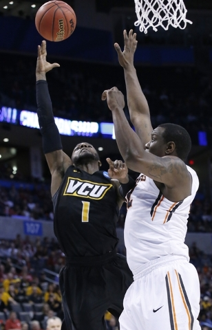 Virginia Commonwealth guard JeQuan Lewis (1) is fouled by Oregon State forward Jarmal Reid, right, as he shoots in the first half of a first-round men's college basketball game in the NCAA Tournam ...
