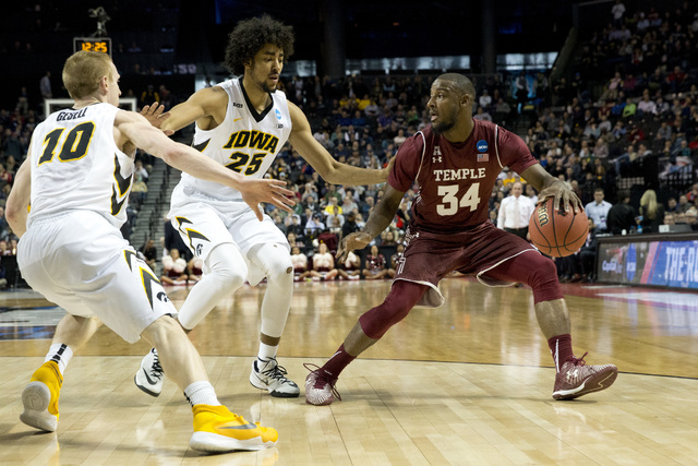 Temple guard Devin Coleman (34) drives to the basket against Iowa guard Mike Gesell (10) and forward Dom Uhl (25) during the first half of a first round men's college basketball game in the NCAA T ...