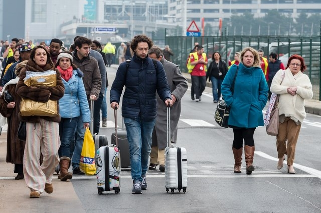 People walk away from Brussels airport after explosions rocked the facility in Brussels, Belgium Tuesday March 22, 2016. Explosions rocked the Brussels airport and the subway system Tuesday, just  ...