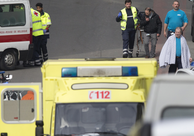 A victim wearing a blanket is evacuated by emergency services after a explosion in a main metro station in Brussels on Tuesday, March 22, 2016. Explosions rocked the Brussels airport and the subwa ...