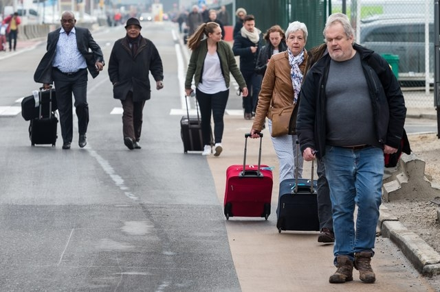 People walk away from Brussels airport after explosions rocked the facility in Brussels, Belgium Tuesday March 22, 2016.   Explosions rocked the Brussels airport and the subway system Tuesday, jus ...