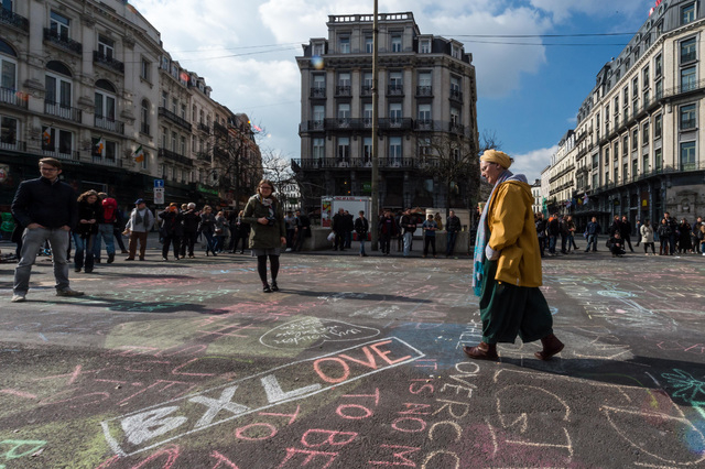 A man walks by solidarity messages written in chalk outside the stock exchange in Brussels on Tuesday, March 22, 2016. Explosions, at least one likely caused by a suicide bomber, rocked the Brusse ...