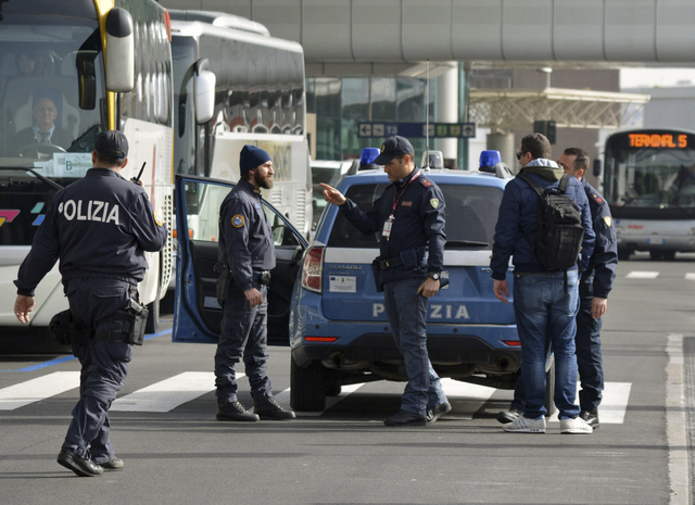 Police officers perform security checks at Fiumicino airport, near Rome, Tuesday, March 22, 2016. The Italian Interior Ministry announced heightened security measures at major Italian airports fol ...