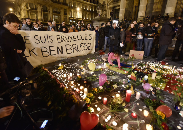 """People holding a banner reading """"I am Brussels"""" behind flowers and candles to mourn for the victims at Place de la Bourse in the center of Brussels, Tuesday, March 22, 2016. Bomb ..."""