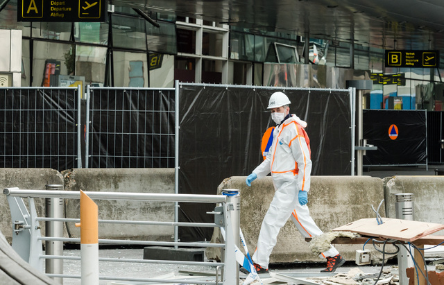 A forensics officer works in front of the damaged Zaventem Airport terminal in Brussels on Wednesday, March 23, 2016. Belgian authorities were searching Wednesday for a top suspect in the country' ...