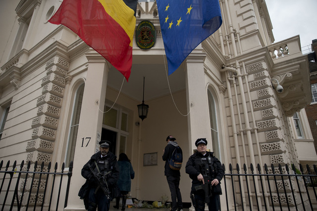 Armed British police stand guard outside the Belgian Embassy in London, Wednesday, March 23, 2016. Belgian authorities searched Wednesday for a man pictured at the Brussels airport with two appare ...