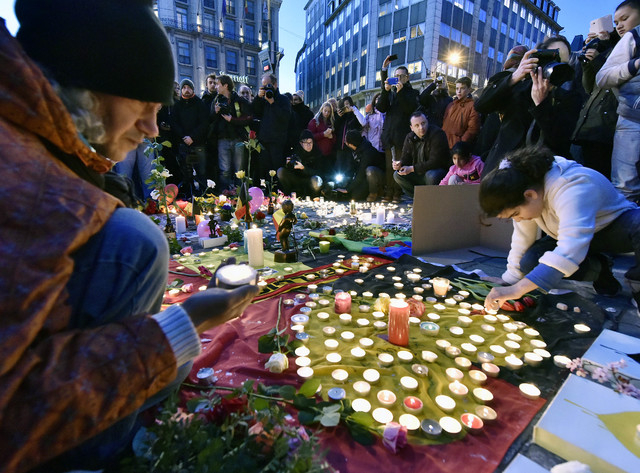 People bring flowers and candles to mourn for the victims at Place de la Bourse in the center of Brussels, Tuesday, March 22, 2016. Bombs exploded at the Brussels airport and one of the city's met ...