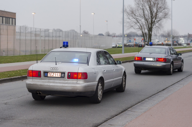 Two police cars, one of them believed to be transporting terror suspect Salah Abdeslam, leave the prison in Bruges, Belgium Thursday, March 24, 2016. Abdeslam, the chief suspect in last year's dea ...