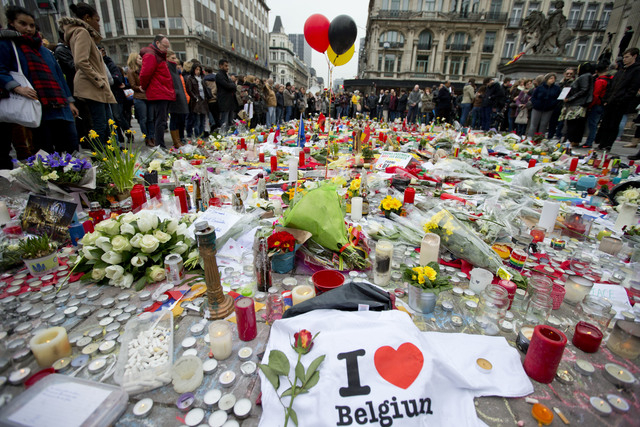 Three balloons in the colors of the Belgian flag fly as people mourn for the victims of the bombings at the Place de la Bourse in the center of Brussels, Belgium, Thursday, March 24, 2016. The Isl ...