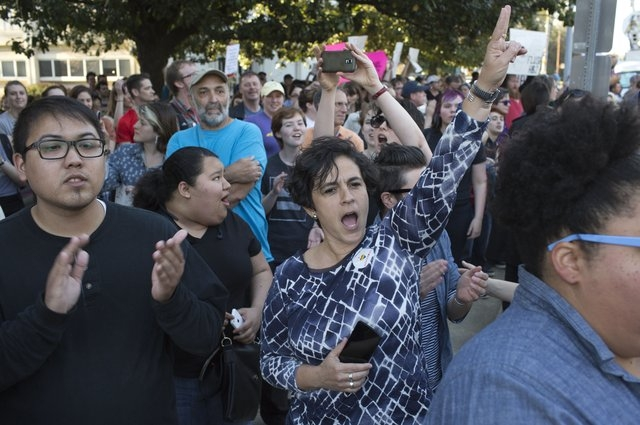 Rajiv Soni, left, and Amara Perez, right, clap and shout as a car driving by honks during a protest against House Bill 2 Thursday, March 24, 2016 outside of the Governor's Mansion on North Blount  ...