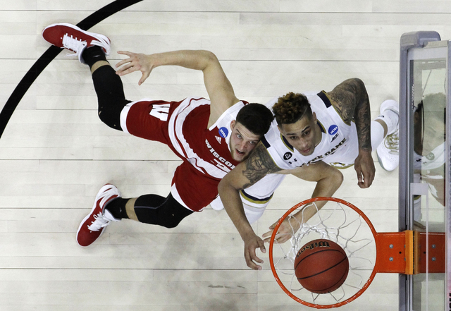 Wisconsin's Zak Showalter, left, and Notre Dame's Zach Auguste vie for position on a rebound during the second half of an NCAA college basketball game in the regional semifinals of the men's NCAA  ...