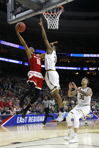 Wisconsin's Jordan Hill, left, shoots against Notre Dame's V.J. Beachem, center, and Zach Auguste during the second half of an NCAA college basketball game in the regional semifinals of the men's  ...