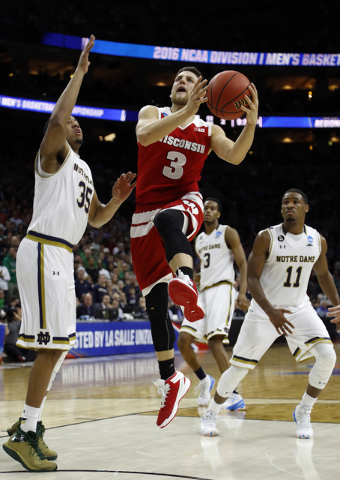 Wisconsin's Zak Showalter (3) goes up for a shot past Notre Dame's Bonzie Colson (35), V.J. Beachem (3) and Demetrius Jackson (11) during the second half of an NCAA college basketball game in the  ...