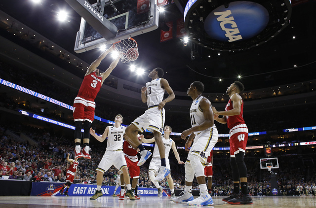 Wisconsin's Zak Showalter (3) dunks as Notre Dame's V.J. Beachem (3) and Steve Vasturia (32) watch during the second half of an NCAA college basketball game in the regional semifinals of the men's ...