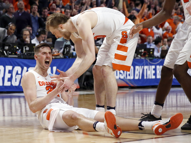 Syracuse's Tyler Lydon (20) celebrates with Trevor Cooney (10) after getting fouled in the final seconds of a college basketball game in the regional semifinals of the NCAA Tournament, Friday, Mar ...