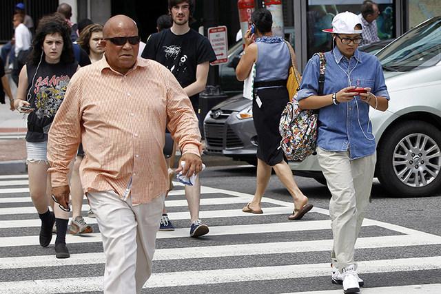 Pedestrians text messages while crossing the street in downtown Washington. (AP Photo/Pablo Martinez Monsivais)