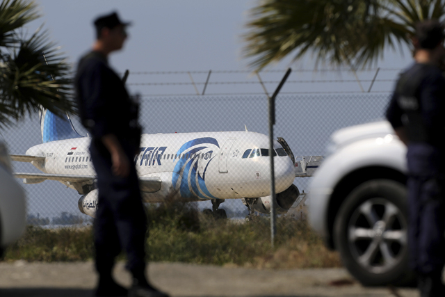 Police officers stand guards by the fence of the airport as a hijacked EgyptAir aircraft is seen after landing at Larnaca Airport in Cyprus Tuesday, March 29, 2016. The EgyptAir plane was hijacked ...