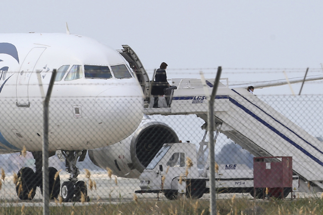 A passenger leaves a hijacked EgyptAir aircraft after landing at Larnaca Airport in Cyprus Tuesday, March 29, 2016. An Egyptian man hijacked the EgyptAir plane Tuesday and forced it to land in Cyp ...
