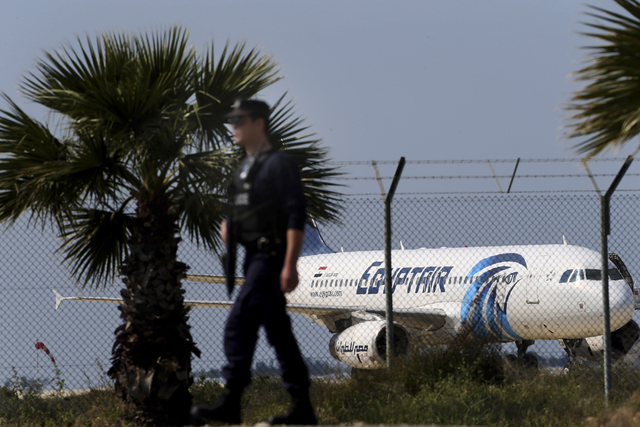 A police officer patrols outside the airport as an hijacked aircraft of EgyptAir is seen after landing at Larnaca Airport in Cyprus Tuesday, March 29, 2016. The EgyptAir plane was hijacked on Tues ...