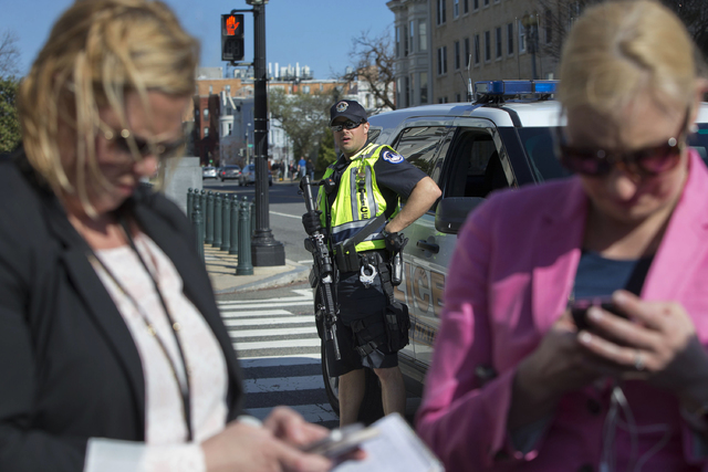 A Capitol Police officer watches as members of the media work in the foreground on Capitol Hill in Washington, Monday, March 28, 2016. Capitol Police officers say a man was shot by police after dr ...