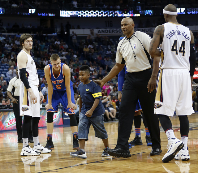 A young boy is sent back to the stands by the referee after he ran onto the court in the second half of an NBA basketball game between the New Orleans Pelicans and the New York Knicks in New Orlea ...