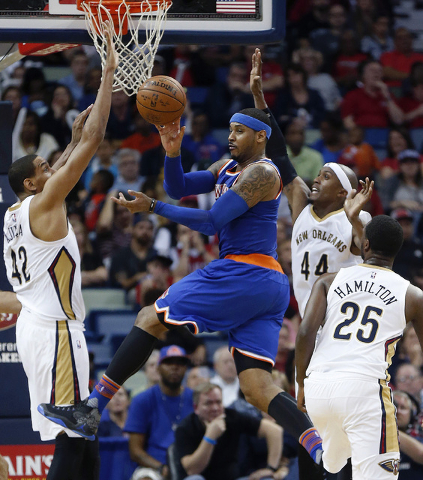 New York Knicks forward Carmelo Anthony (7) passes between New Orleans Pelicans center Alexis Ajinca (42), forward Dante Cunningham (44) and guard Jordan Hamilton (25) in the second half of an NBA ...