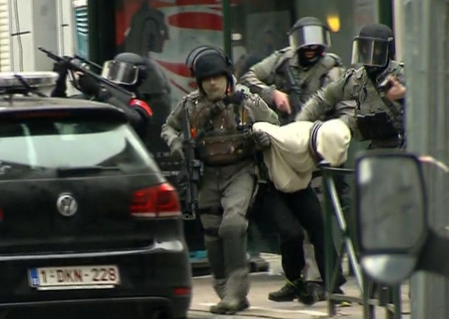In this framegrab taken from VTM, armed police officers escort Salah Abdeslam to a police vehicle during a raid in the Molenbeek neighborhood of Brussels, Belgium, Friday March 18, 2016. (VTM via AP)