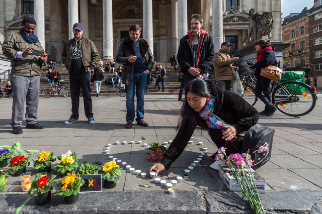 A woman places candles in the shape of a heart outside the stock exchange in Brussels on Tuesday, March 22, 2016. Explosions, at least one likely caused by a suicide bomber, rocked the Brussels ai ...