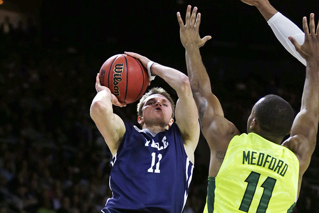 Yale guard Makai Mason, left, leaps and shoots over Baylor guard Lester Medford in the first half during the first round of the NCAA college men's basketball tournament in Providence, R.I., Thursd ...
