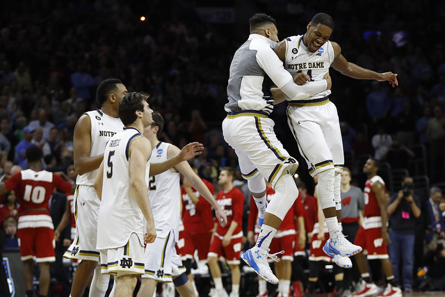 Notre Dame's Demetrius Jackson, right, celebrates with teammates after a steal from Wisconsin n the final seconds of an NCAA college basketball game in the regional semifinals of the men's NCAA To ...