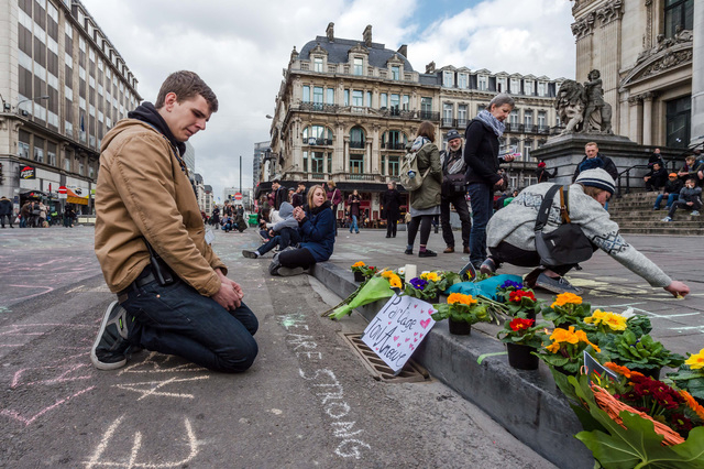 A man looks at flowers and messages outside the stock exchange in Brussels on Tuesday, March 22, 2016. Explosions, at least one likely caused by a suicide bomber, rocked the Brussels airport and s ...