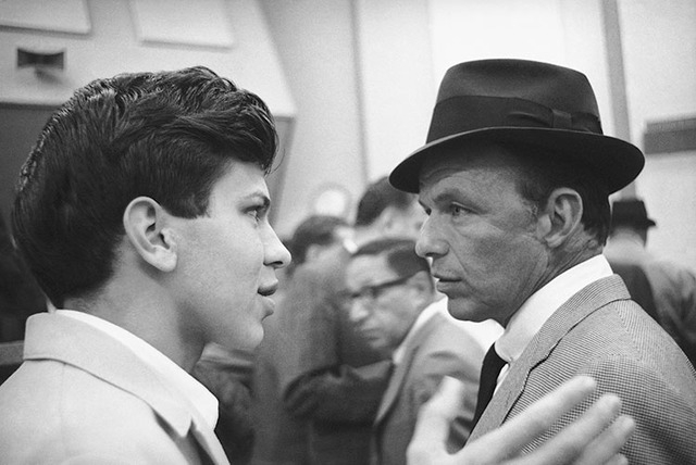 Frank Sinatra Jr. talks with his father on Dec. 7, 1962.  (AP Photo)