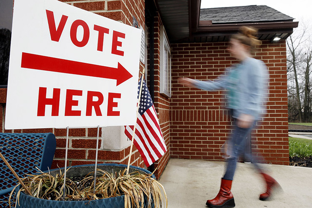 A woman arrives to vote in the primary election Tuesday, March 15, 2016. (AP Photo/Matt Rourke)