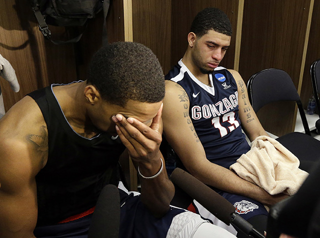 Gonzaga's Eric McClellan (23) and Josh Perkins (13) embrace in the locker room after an NCAA college basketball game in the regional semifinals of the NCAA Tournament, Friday, March 25, 2016, in C ...
