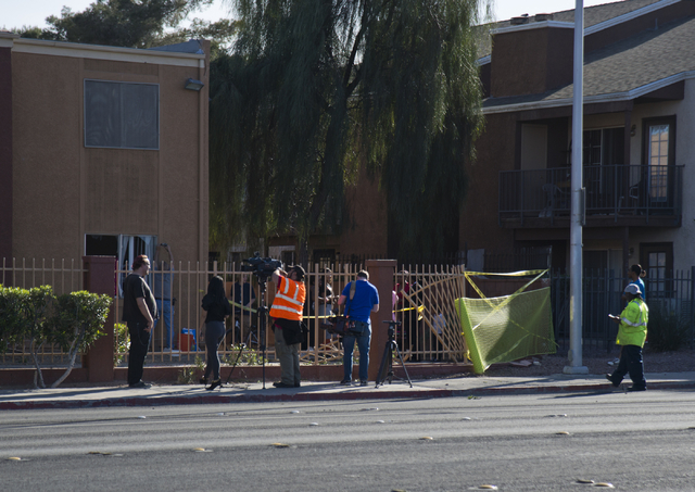 People stand on the sidewalk near where a car crashed through a fence and into a building at the Promenade at Sahara apartment complex near Sahara Avenue and Nellis Boulevard on Tuesday, March 8,  ...