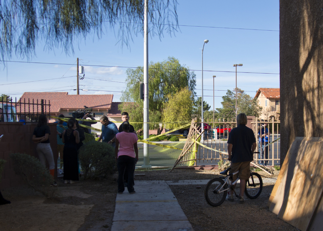 People stand near where a car crashed through a fence and into a building at the Promenade at Sahara apartment complex near Sahara Avenue and Nellis Boulevard on Tuesday, March 8, 2016. Daniel Cla ...