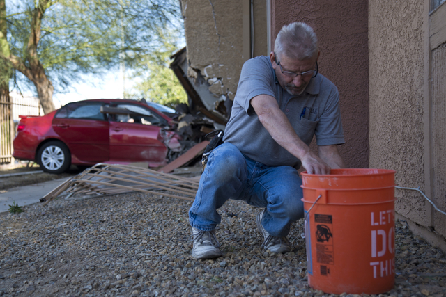 A man who would not give his name cleans broken glass near a car that crashed through a fence and into a building at the Promenade at Sahara apartment complex near Sahara Avenue and Nellis Bouleva ...