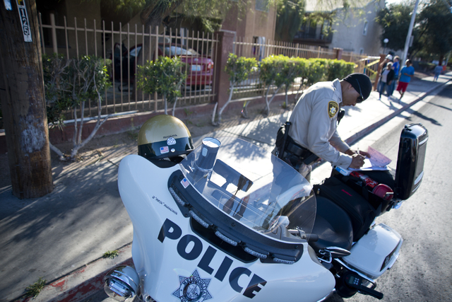 Officer Duane Nakagawa fills out paperwork near a car that crashed through a fence and into a building at the Promenade at Sahara apartment complex near Sahara Avenue and Nellis Boulevard on Tuesd ...