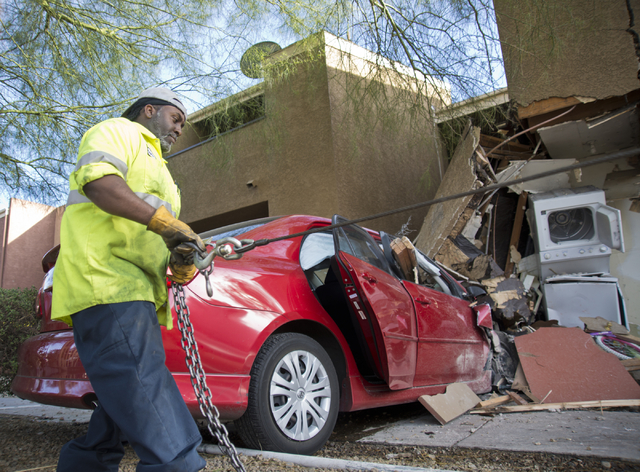 Stephen from Fast Towing prepares to remove a car that crashed through a fence and into a building at the Promenade at Sahara apartment complex near Sahara Avenue and Nellis Boulevard on Tuesday,  ...
