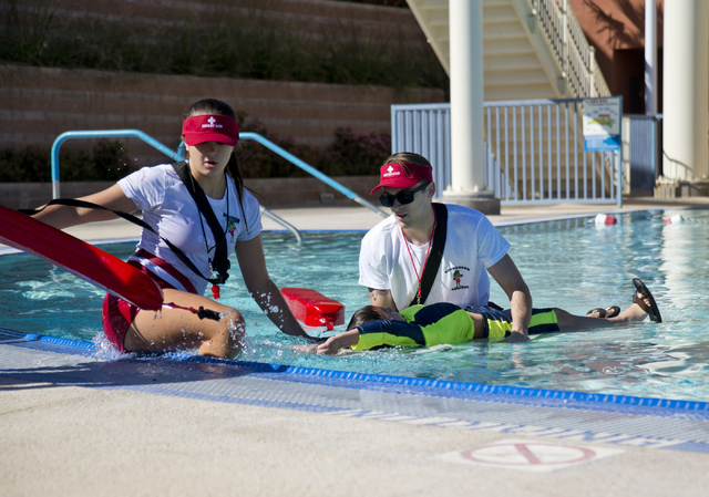 Christina Beaver, left, and Donavan Govenor participate in the mock rescue of Benjamin Hickman during the April Pools Day event at the Henderson Multigenerational Aquatic Complex in Henderson on T ...