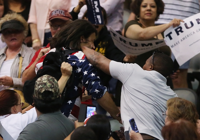 Trump protester Bryan Sanders, center left, is punched by a Trump supporter as he is escorted out of Republican presidential candidate Donald Trump's rally at the Tucson Arena in downtown Tucson,  ...