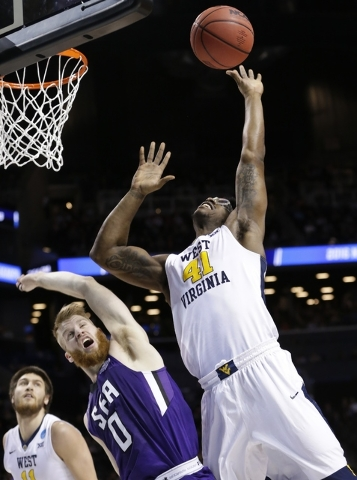 West Virginia's Devin Williams (41) and Stephen F. Austin's Thomas Walkup (0) fight for the ball during the first half of a first-round men's college basketball game in the NCAA Tournament,Friday, ...