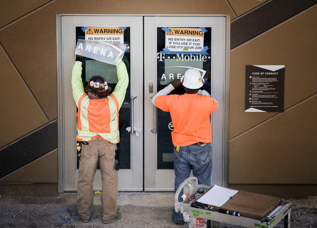 Workmen place signage on doors at theT-Mobile Arena behind New York-New York on Monday, Feb. 29, 2016. The joint venture partners AEG and MGM Resorts is scheduled to open the arena next month. Jef ...