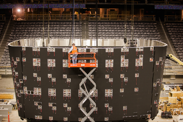 A man works on the T-Mobile Arena scoreboard behind New York-New York on Monday, Feb. 29, 2016. The joint venture partners AEG and MGM Resorts is scheduled to open the arena next month. Jeff Schei ...