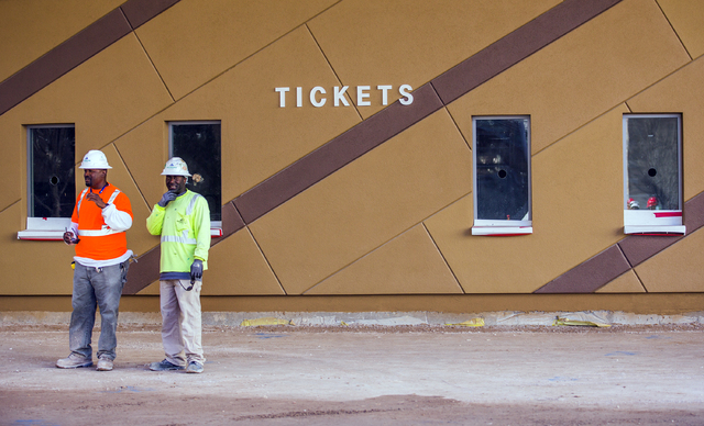 Workers stand near the ticket windows at the T-Mobile Arena behind New York-New York on Monday, Feb. 29, 2016. The joint venture partners AEG and MGM Resorts is scheduled to open the arena next mo ...