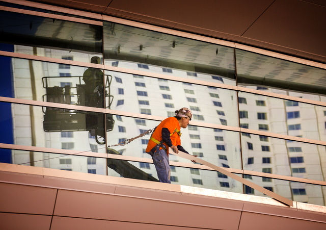 A worker places stripping on the T-Mobile Arena behind New York-New York on Monday, Feb. 29, 2016. The joint venture partners AEG and MGM Resorts is scheduled to open the arena next month. Jeff Sc ...
