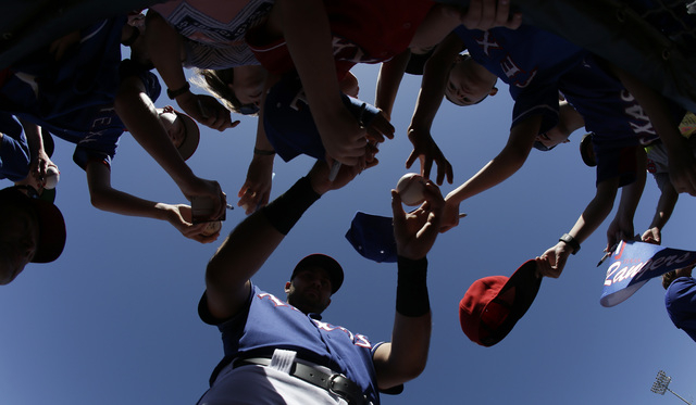 Texas Rangers' Joey Gallo gives autographs before a spring training baseball game against the Oakland Athletics on Saturday, March 12, 2016, in Surprise, Ariz. (AP Photo/Darron Cummings)