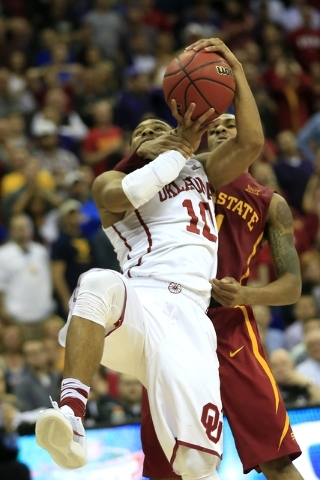 Oklahoma guard Jordan Woodard (10) is fouled by Iowa State guard Monte Morris, back, during the second half of an NCAA college basketball game in the quarterfinals of the Big 12 conference tournam ...