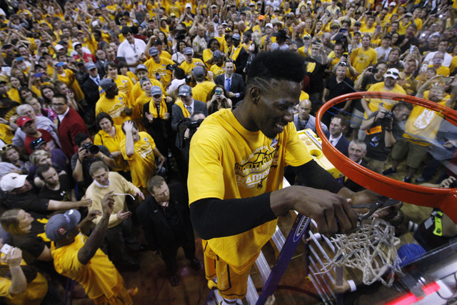 Wyoming forward Derek Cooke Jr. cuts down a piece of net after their Mountain West Conference tournament championship game against San Diego State Saturday, March 14, 2015. Wyoming upset San Diego ...