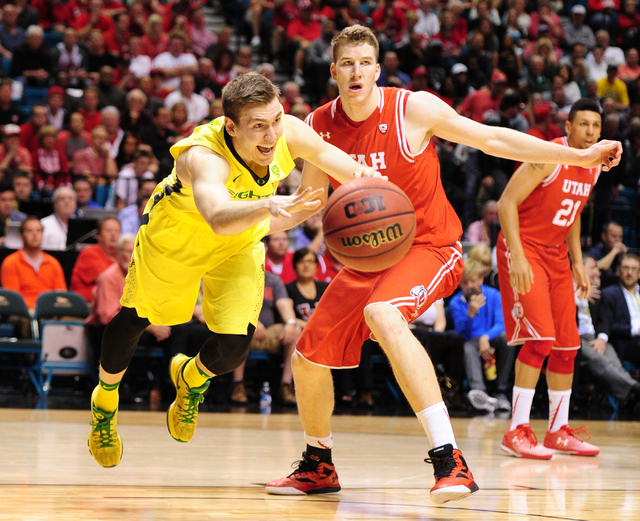 Oregon guard Casey Benson falls while passing in front of Utah forward Jakob Poeltl in the first half of the Pac 12 Conference tournament championship game at the MGM Grand Garden Arena in Las Veg ...
